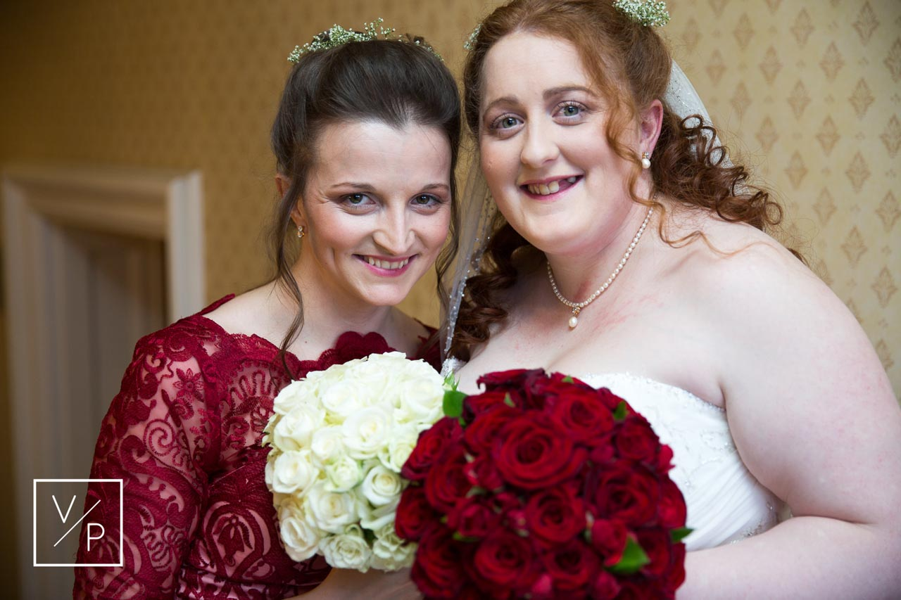 Bridesmaid and Bride with red and white roses. Horwood House wedding at Easter. Veiled Productions.