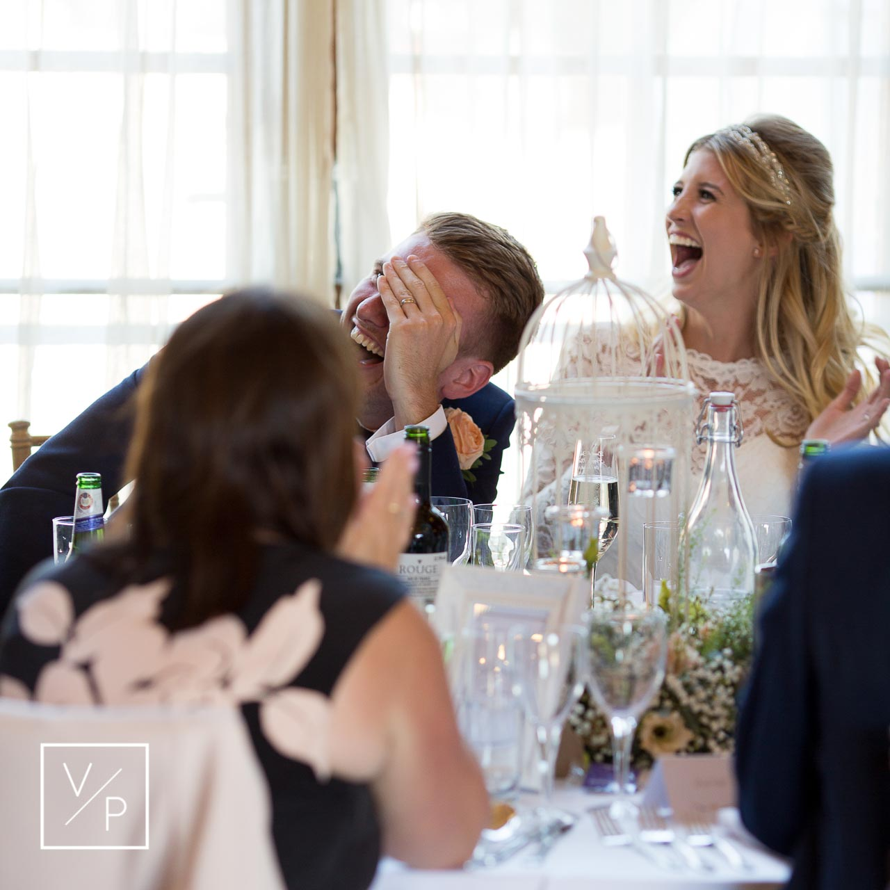 Christina and Dan laughing during the speeches - The Great Barn wedding videographer Veiled Productions
