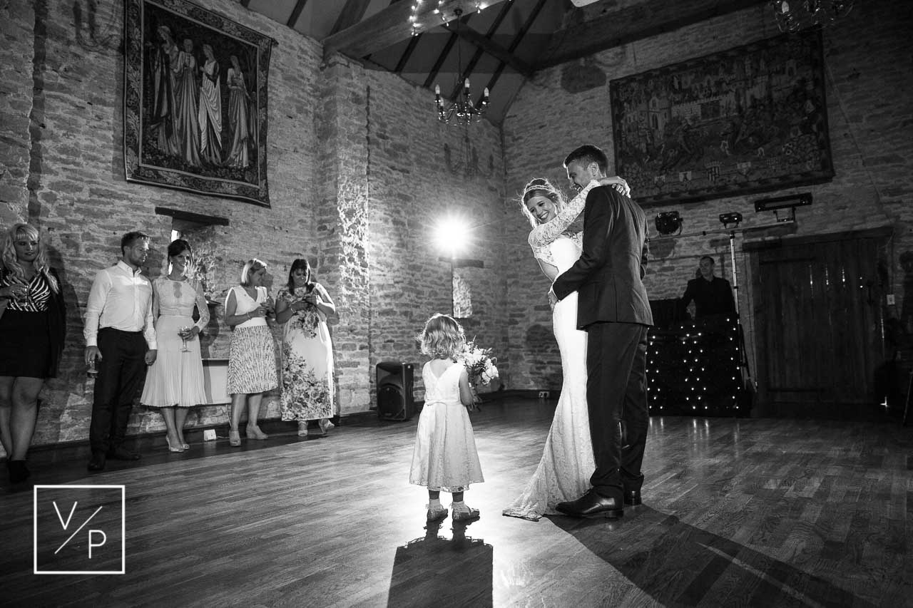 Christina and Dan's flower girl stealing the show during the first dance holding the bridal bouquet. The Great Barn Aynho wedding videographer Veiled Productions