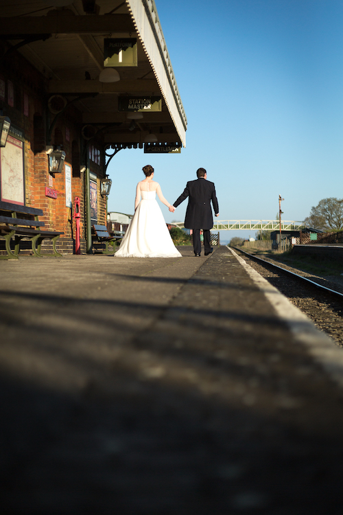 Buckinghamshire Railway Centre wedding video example - Emma and James walking hand in hand down the platform. Photographed and filmed by Veiled Productions