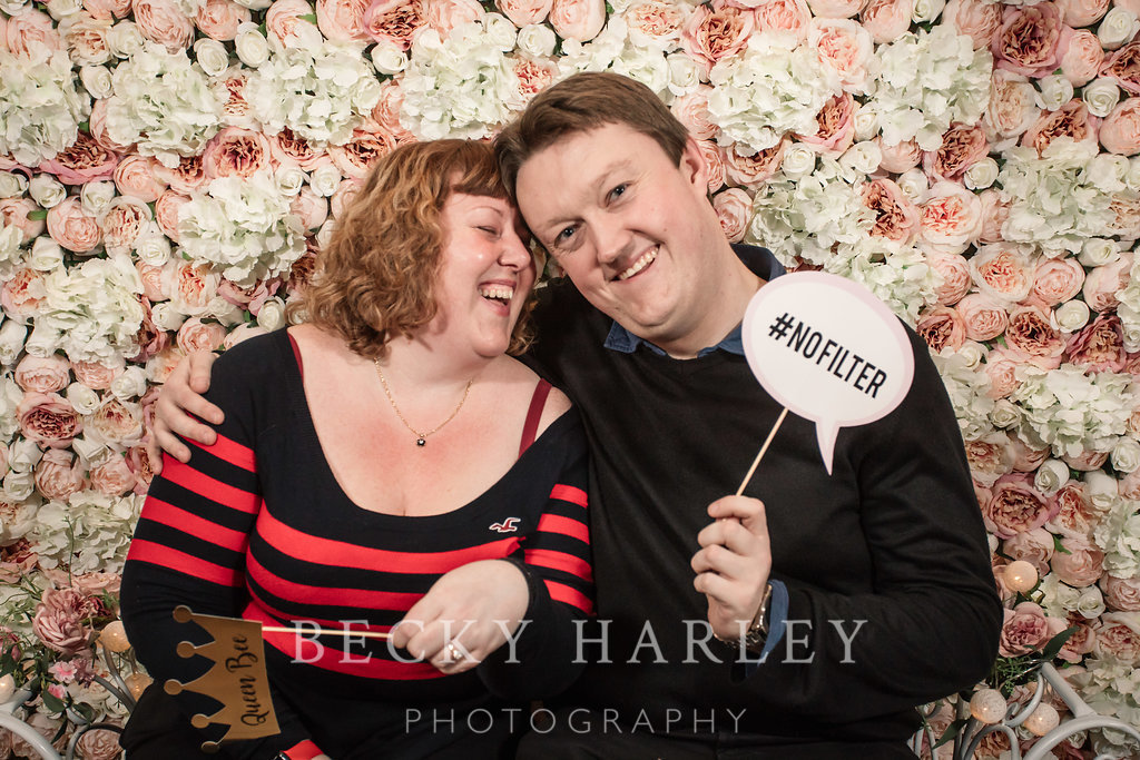 A couple in the flower wall photo booth at the Engage Wedding Planning Party Coltsfoot Country Retreat photo courtesy of Becky Harley Photography