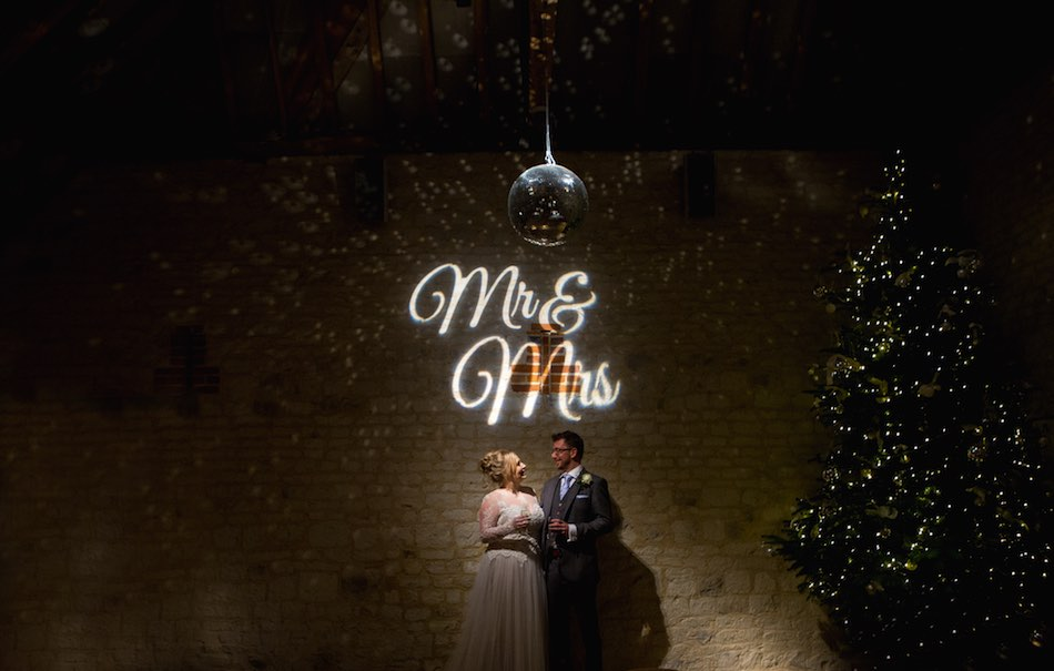 Hannah and Mike under the Mr and Mrs sign at Bury Court Barn next to the Christmas tree - Photography by Em J Photo and Videography by Veiled Productions