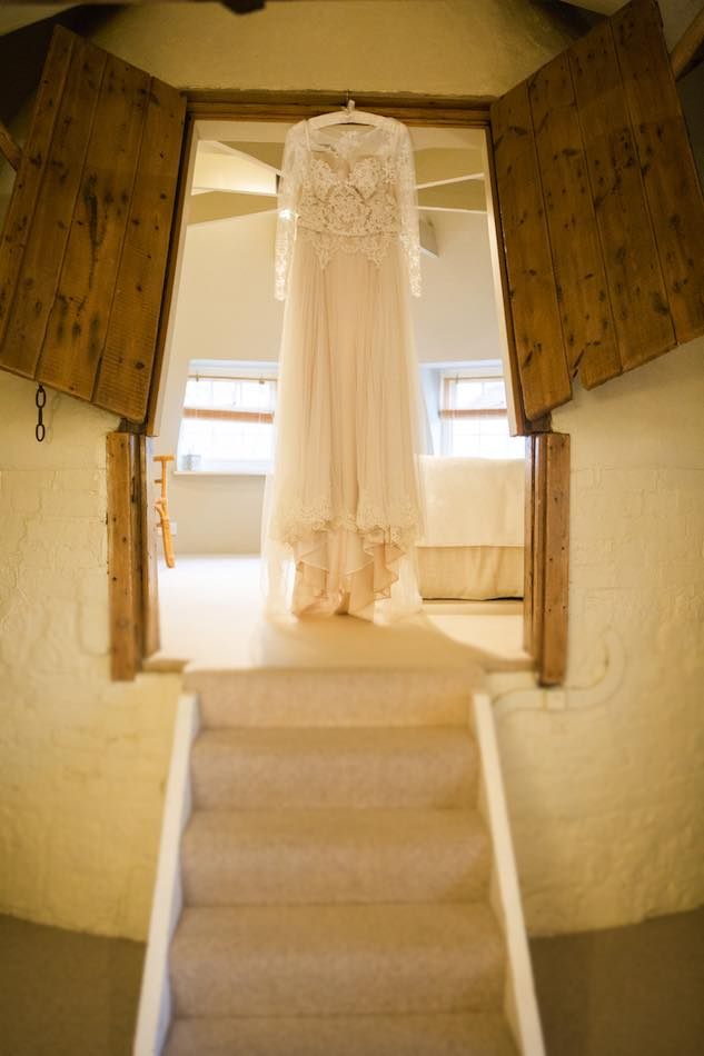 Pros of Winter Weddings - Hannah wedding dress hanging proudly at Bury Court Barn. Photo thanks to Em J Photography