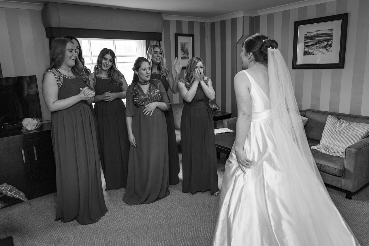 Liz's Bridesmaids seeing her in her wedding dress for the first time. Veiled Productions - Pembroke Lodge Wedding-Liz And Luke | Bride in White wedding day traditions