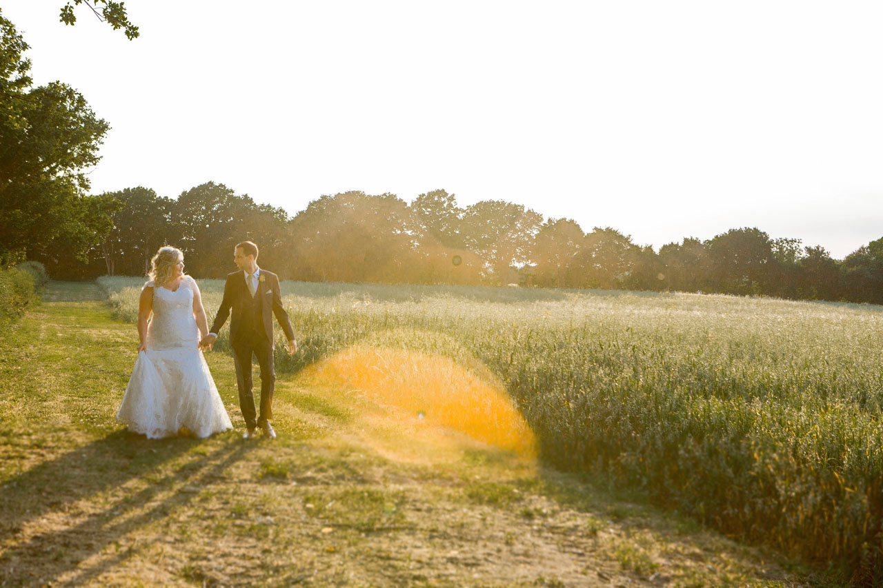 Claire and Andy walking at sunset. Photo thanks to Em J Photography. Colville Hall Wedding Videographer Veiled Productions