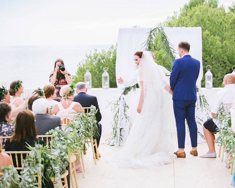 Photo of Katrina Matthews Photography photographing an outdoor wedding ceremony by Laura Beth Photography. Questions to ask your wedding photographer: will there be a second shooter?