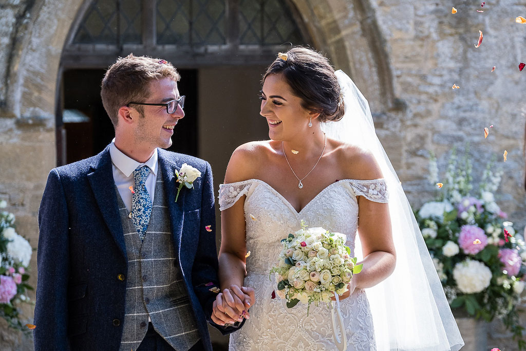 Rebecca and Mark exiting their church wedding ceremony as newlyweds - photography by Rob Wheal Photography | Oxfordshire wedding videography by Veiled Productions
