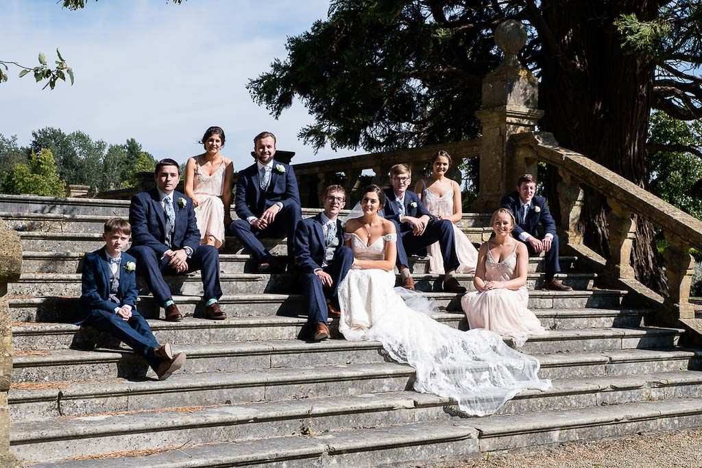 Rebecca and Mark wedding party - bridesmaids and groomsmen on the steps at Eynsham Hall - photography by Rob Wheal Photography | Oxfordshire wedding videography by Veiled Productions