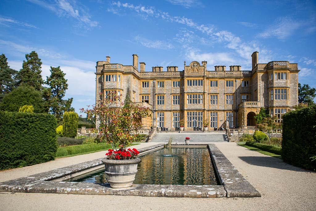 View of Eynsham Hall from the landscaped gardens with the pond in the centre - photography by Rob Wheal Photography | Oxfordshire wedding videography by Veiled Productions
