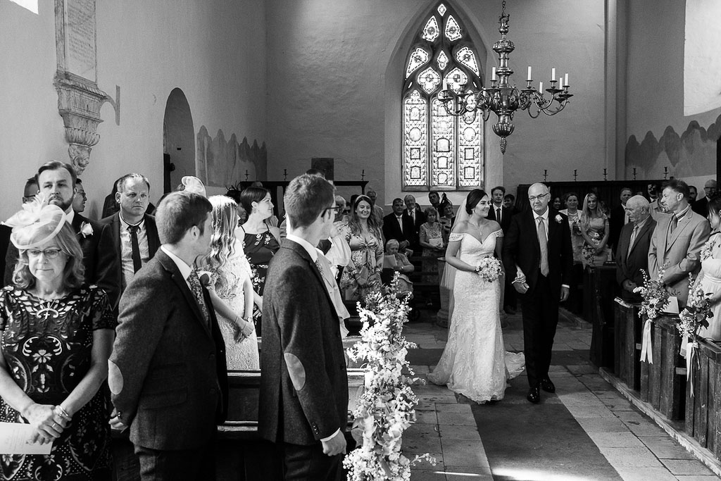 Rebecca walking down the aisle with her Dad - photography by Rob Wheal Photography | Oxfordshire wedding videography by Veiled Productions