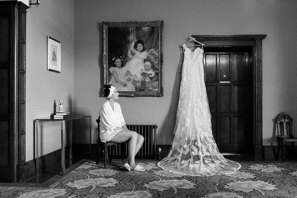 Rebecca getting ready for her wedding ceremony looking up at her wedding dress - photography by Rob Wheal Photography | Oxfordshire Wedding Videography by Veiled Productions