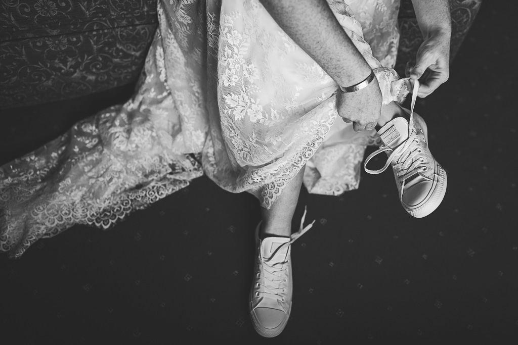 Rachel tying the laces on her wedding day Converse white shoes. Photography by Tiree Dawson Photography. Videography by Veiled Productions. Sophisticated New House Farm wedding in the Summer 2019.