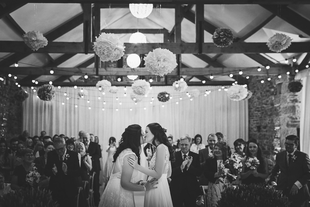 Kay and Rach first kiss as newlyweds. Sophisticated Barn Wedding. Photography by Tiree Dawson Photography. Videography by Veiled Productions. Sophisticated New House Farm wedding in the Summer 2019.