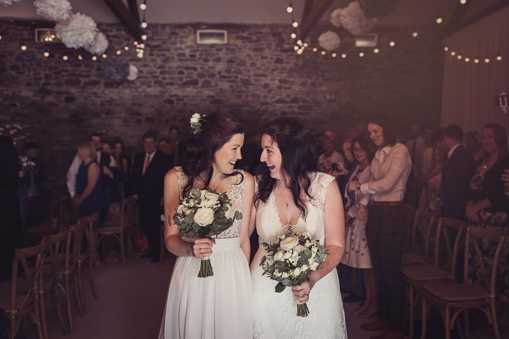 Kay and Rach leaving their ceremony as newlyweds. Sophisticated Barn Wedding. Photography by Tiree Dawson Photography. Videography by Veiled Productions. Flowers by Floral Boutique Cockermouth. Sophisticated New House Farm wedding in the Summer 2019.
