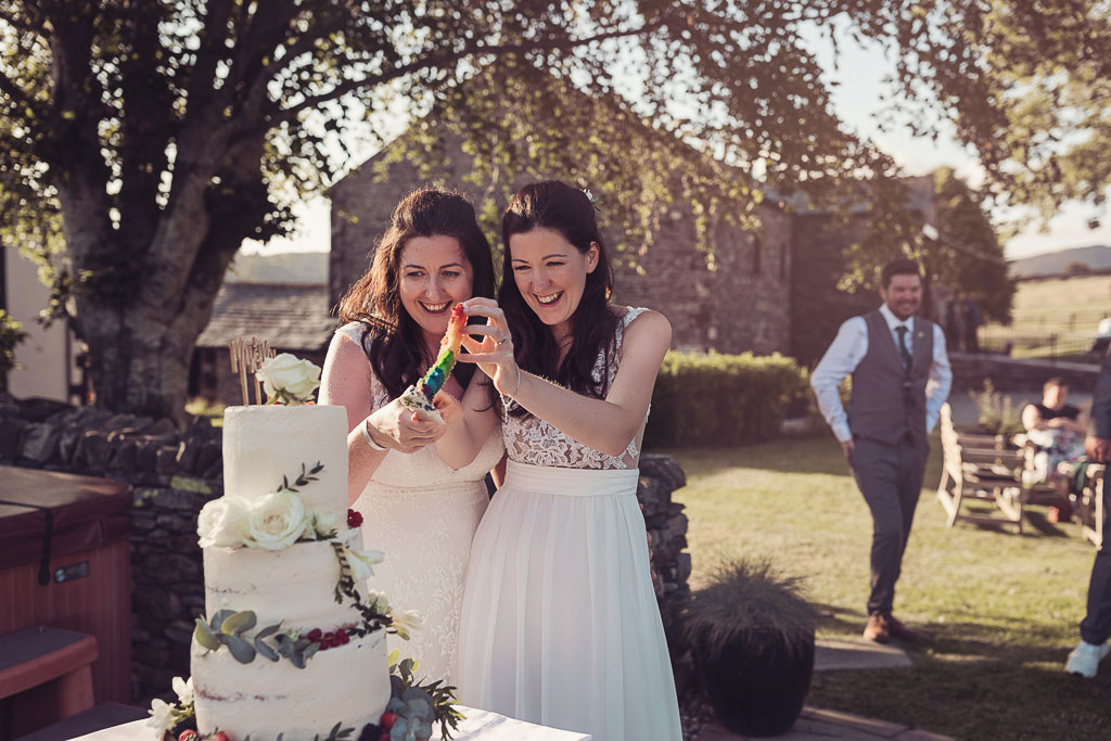 Kay and Rach cutting their wedding cake revealing rainbow coloured layers. Sophisticated Barn Wedding. Photography by Tiree Dawson Photography. Videography by Veiled Productions. Sophisticated New House Farm wedding in the Summer 2019. Cake made by Baba Ganoush Catering York.